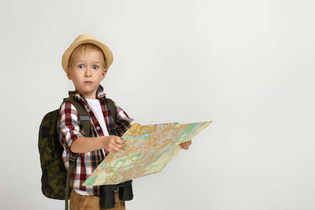 Little boy tourist with backpack holding binoculars and map. child is looking on the map. Little boy scout dreams of traveling. copy space
