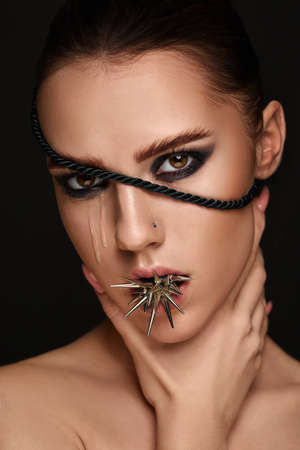 portrait of fashion model girl with metal spikes and dark make-up. art makeup