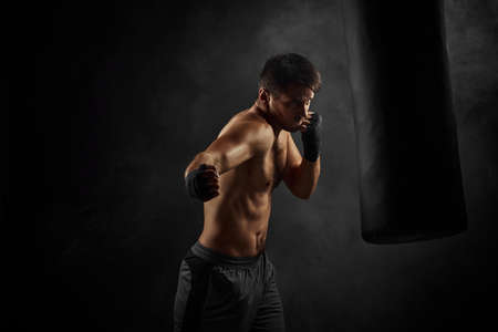 Male boxer training defense and attacks in boxing bag on black background
