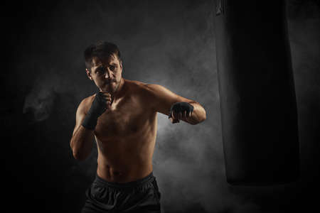 sporty shirtless boxer in black boxing wraps punching in boxing bag on dark background with smoke