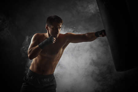 Aggressive boxer in black boxing wraps punching in boxing bag on dark background with smoke Zdjęcie Seryjne
