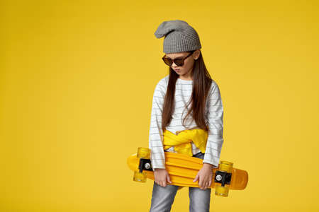 unhappy little child girl in hat and sunglasses posing with yellow skateboard on studio background.