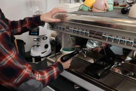 Barista using a coffee machine to make coffee