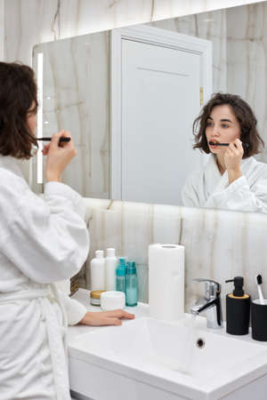 woman in white bathrobes brushing teeth in front of mirror Stock Photo