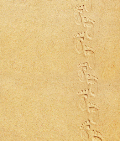 Cute baby footsteps on sandy beach with space for text or desighn