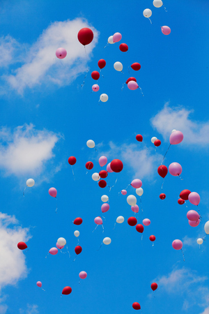 Many released flying balloons in blue sky