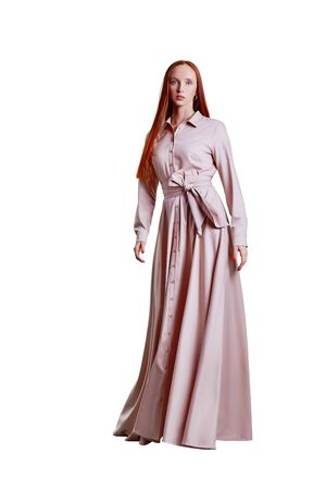 Beautiful red hair women model in pink stylish long cotton dress Banque d'images