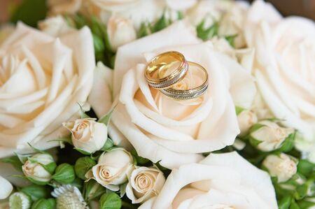 Original wedding rings on beautiful white roses wedding bouquet.