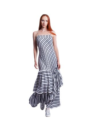 Beautiful young long skinny model with red hair wearing mixed direction lined dress