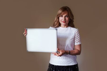 Women teacher lady showing empty whiteboard, smiling, wore classic style