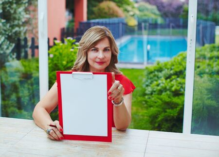 Self employed woman at her luxury home office with pool on background with clipboard in hands