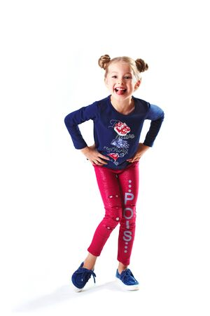 Pretty blondie six years old small girl on white background dancing and showing tongue