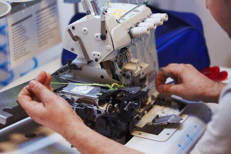 Processus de réparation de machine à coudre et de surjet, mains de maître, outils, détails