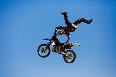Pro motocross rider riding fmx motorbike, jumping performing extreme stunt. Professional biker jumps Stockfoto