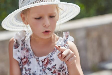 Cute little girl is looking at ladybug and wants it fly