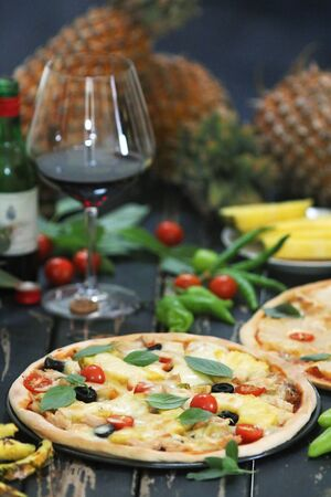Pineapple pizza served with wine Imagens