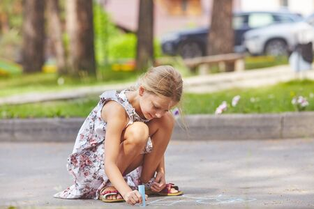 Girl painting on road with chalks