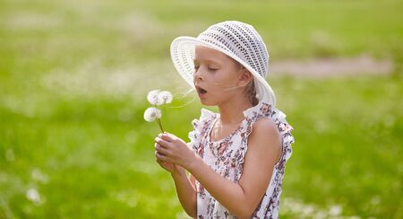 Girl in hat blowing blowball at field 版權商用圖片