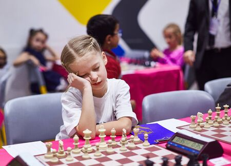 Small cute girl infront of chess board on chess tournament look very bored 版權商用圖片