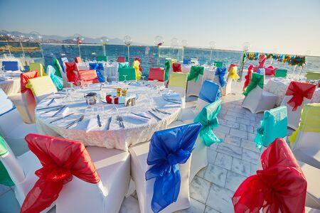 Festive decorated banquet tables on sea view venue 版權商用圖片