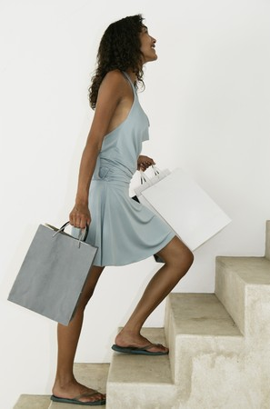 Female walking up stairs with shopping bags Stock Photo