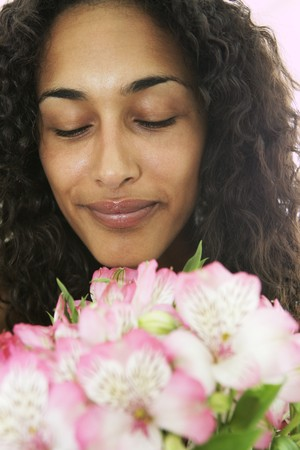 Female smelling flowers with eyes closed