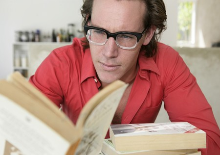 Young man with glasses reading a book