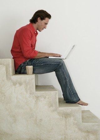 Male working on laptop on stairs at home