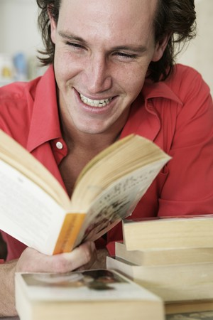 Young man with book in hands reading and laughing