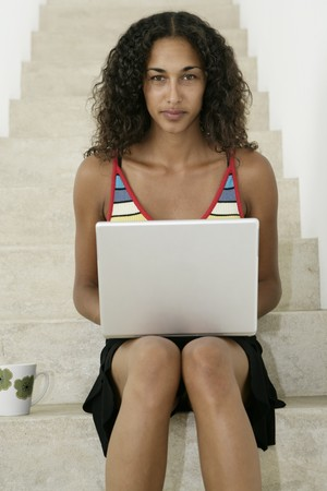 Young female working on laptop on stairs and looking to camera