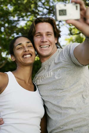 Couple taking self portrait with digital camera Banco de Imagens