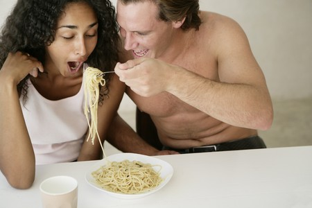 Couple sharing pasta in their kitchen Banco de Imagens