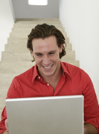 Male smiling and looking at laptop on stairs at home