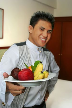 waiter showing fruit in the room, focus on orange Stock Photo