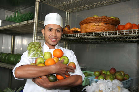 chef holding fruits in refrigerator