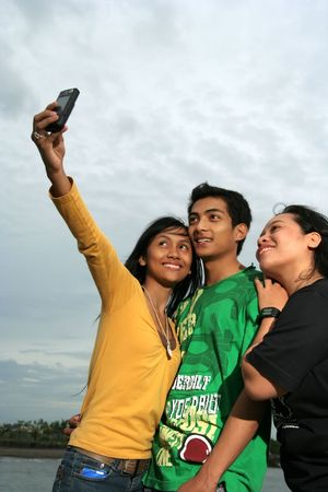 three friend taken photo with mobile phone