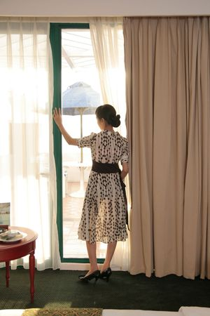 looking out: Woman looking trough of windows in hotel room