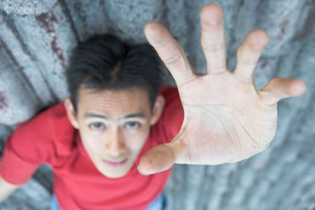 fingers on top: man reaching, focused on hand Stock Photo