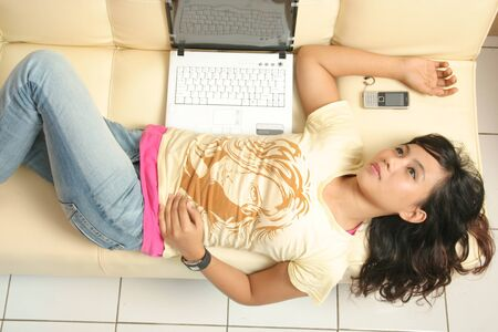 Girl on sofa lie down next by laptop and mobile phone photo