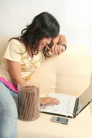 Girl eating cookies while using laptop photo