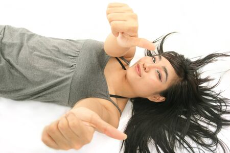 to lie: pretty woman lie down showing thumb up Stock Photo