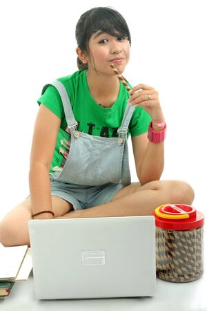 young woman using laptop and eating cookies photo