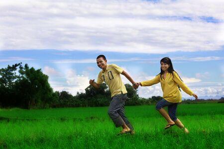 asian happy couple running at rice field Stock Photo