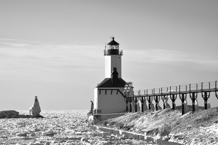 unidentifiable: A black and white winter scene of a lighthouse with an unidentifiable man peering down into icy water