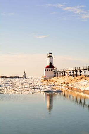 michigan snow: A lighthouse and beacon are shown on a sunny winter day surrounded by icy water and snow-heaped pier