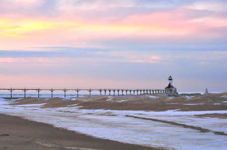 michigan snow: A lighthouse and pier are pictured at sunset with lights on Stock Photo
