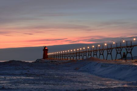 michigan snow: A red lighthouse and pier are pictured lit at dusk in winter