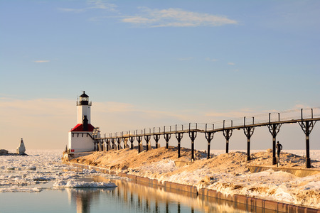 michigan snow: A lighthouse and catwalk pier are pictured on a sunny winter day with an unrecognizable runner headed toward the lighthouse. Stock Photo