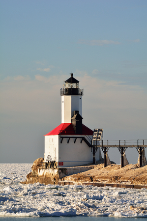 michigan snow: A lighthouse is pictured on a sunny winter day surrounded by icy water Stock Photo