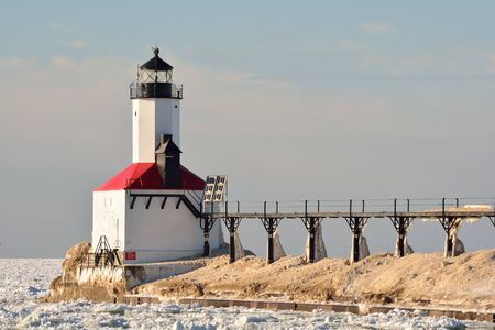 michigan snow: A lighthouse and catwalk pier are pictured on a sunny winter day amid icy water with snow buildup on the pier